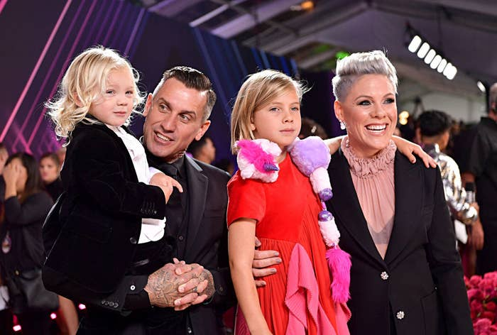 Carey Hart and Pink posing at a Hollywood event with their two children