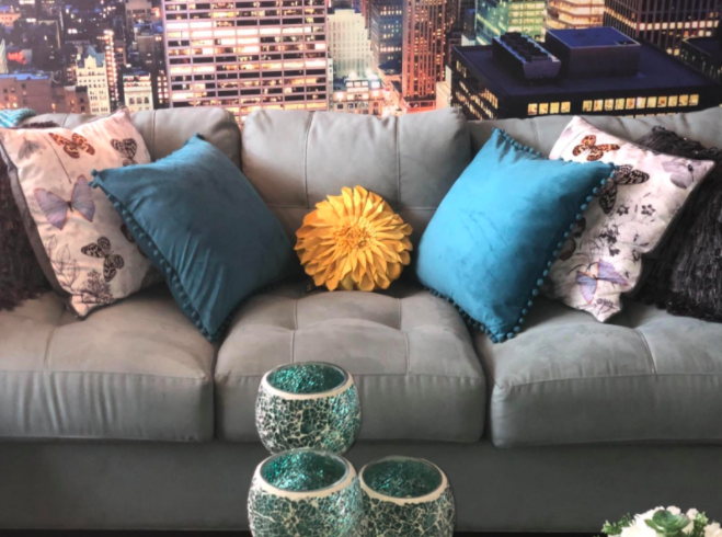 Sunflower accent pillow wedged in between blue pillows and butterfly-pattern pillows on a light gray couch