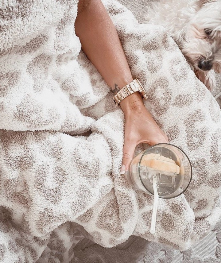 a model wrapped in a leopard print fuzzy blanket in white and light brown