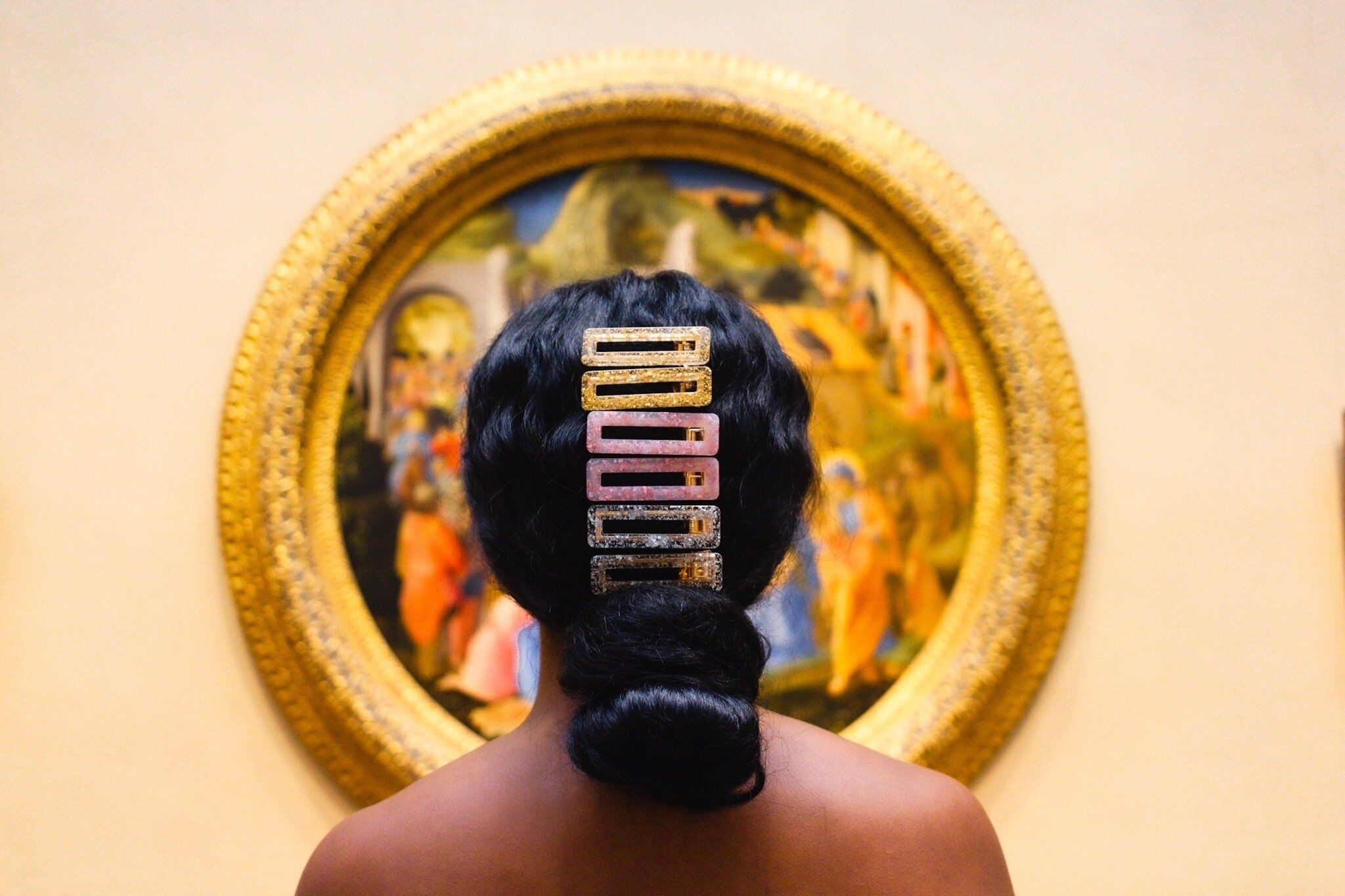Model with six clips above a low bun: two gold, two pink, and two silver