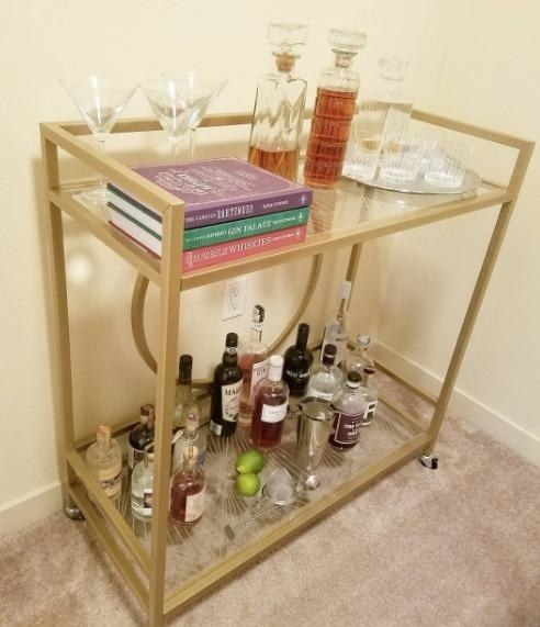 Reviewer pic of the bar cart with two glass-top shelves with a geometric pattern to them  and assorted alcohol bottles and glasses on each one.