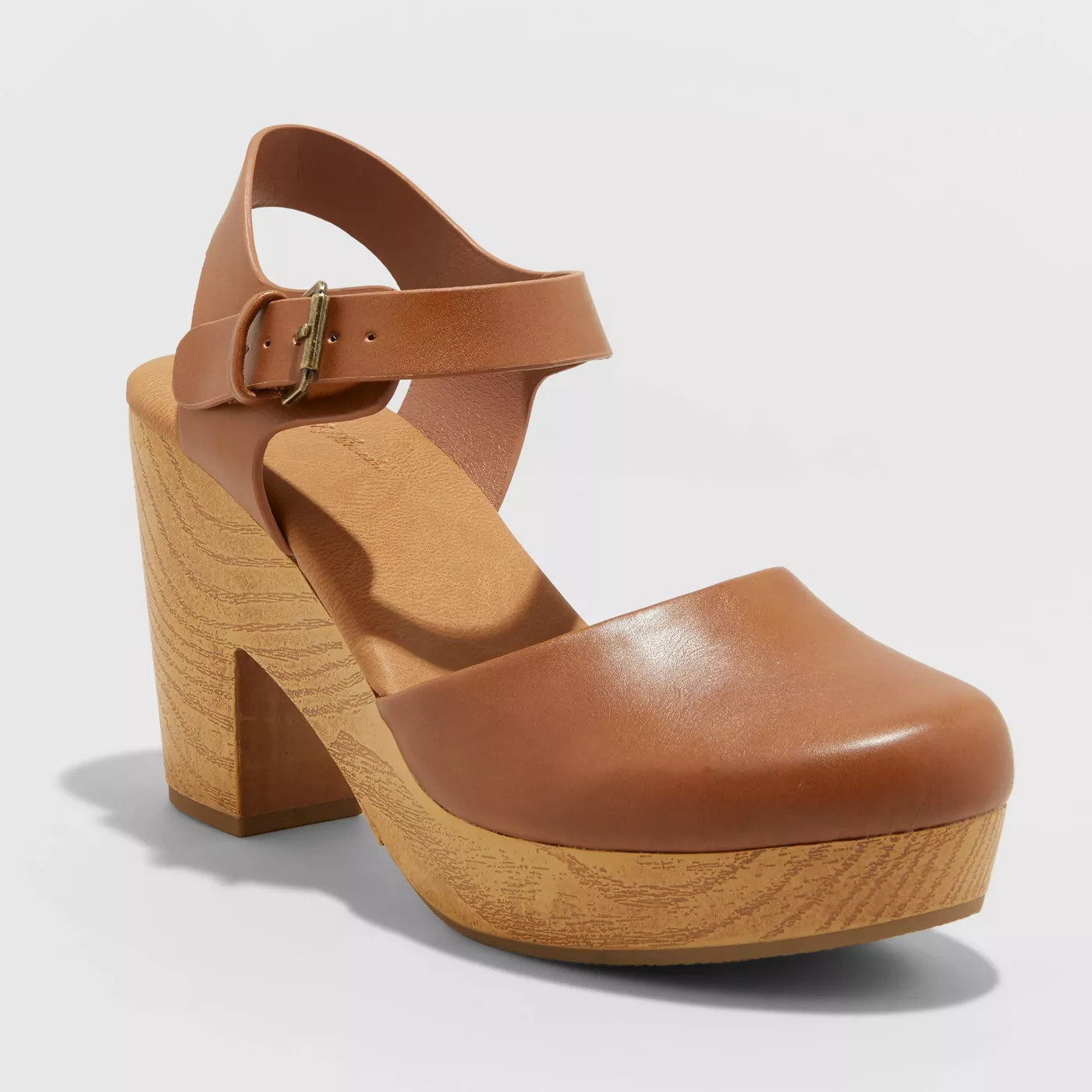 A tan clog wooden sandal with a rounded closed toe and leather straps around the heel.