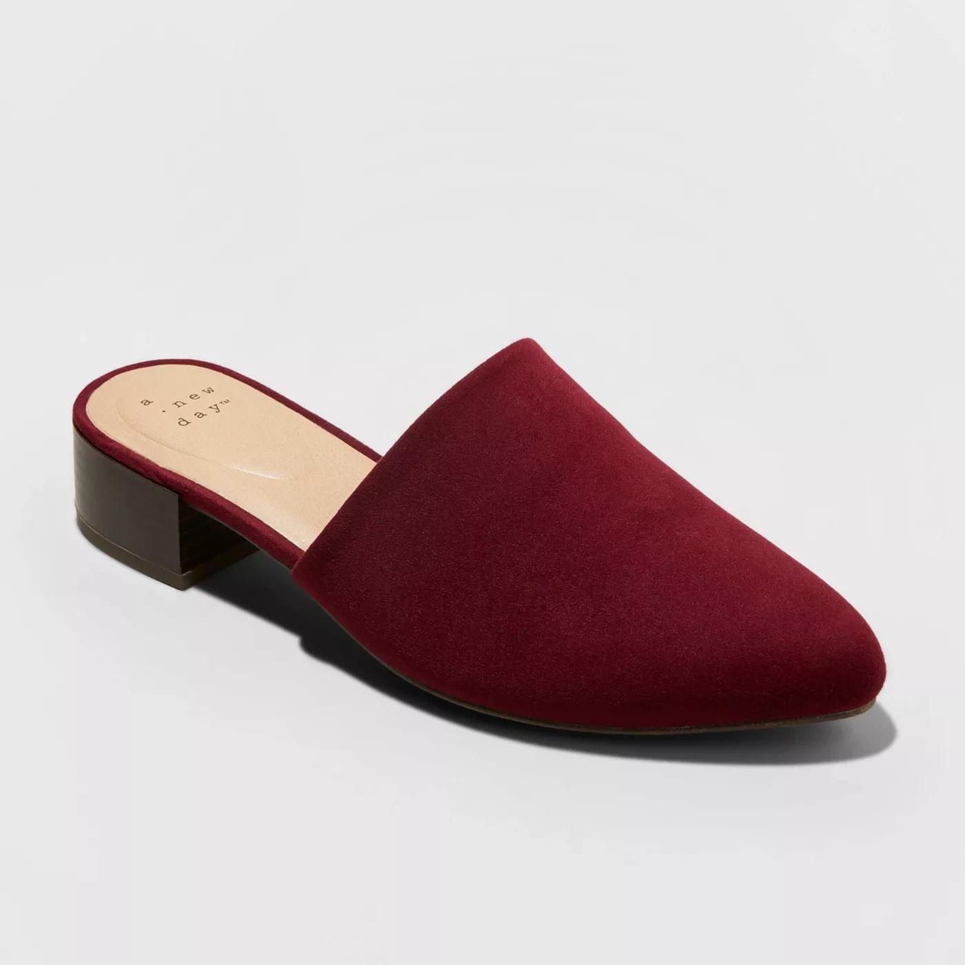 A burgundy mule with a black low block heel