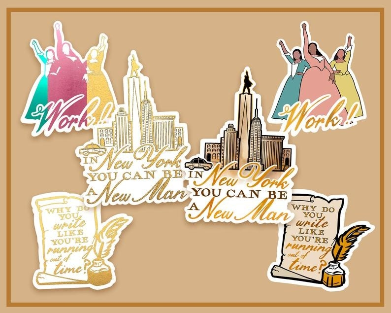 """The foil and glossy versions of the stickers: The silhouettes of the Schuyler sisters and the text """"Work!, an NYC skyline with text """"In New York you can be a new man,"""" and a quill and parchment that reads """"Why do you write like you're running out of time"""""""