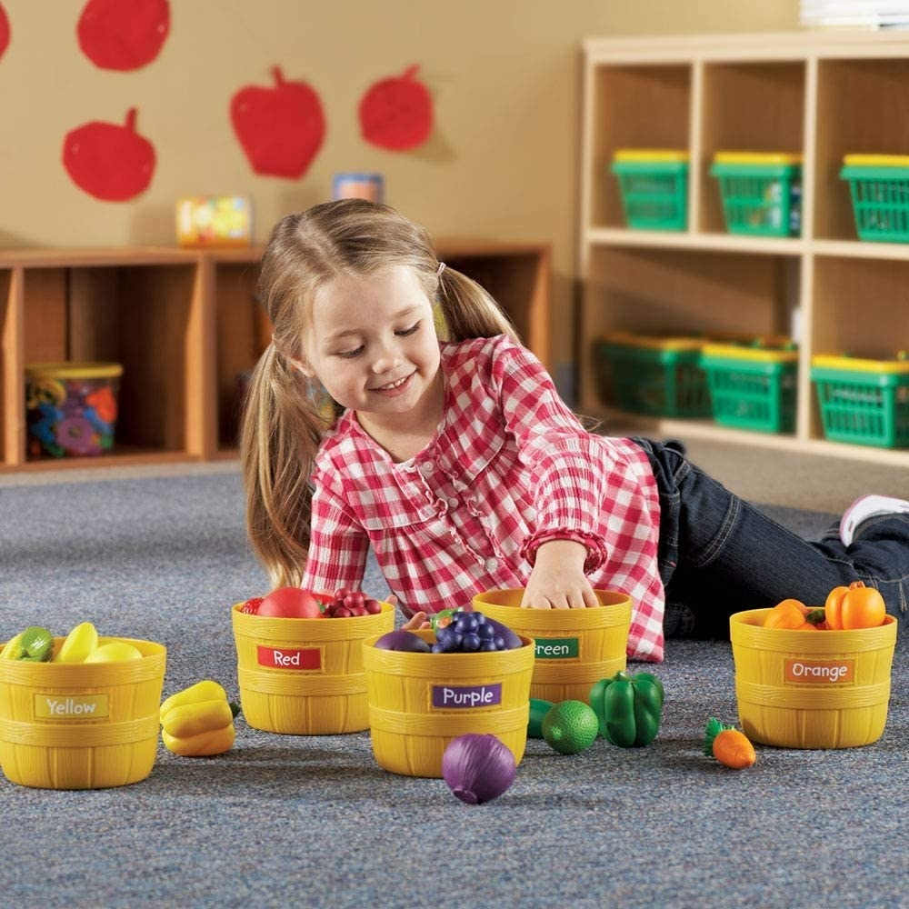 Child model playing with yellow plastic bins filled with color-coded fruit