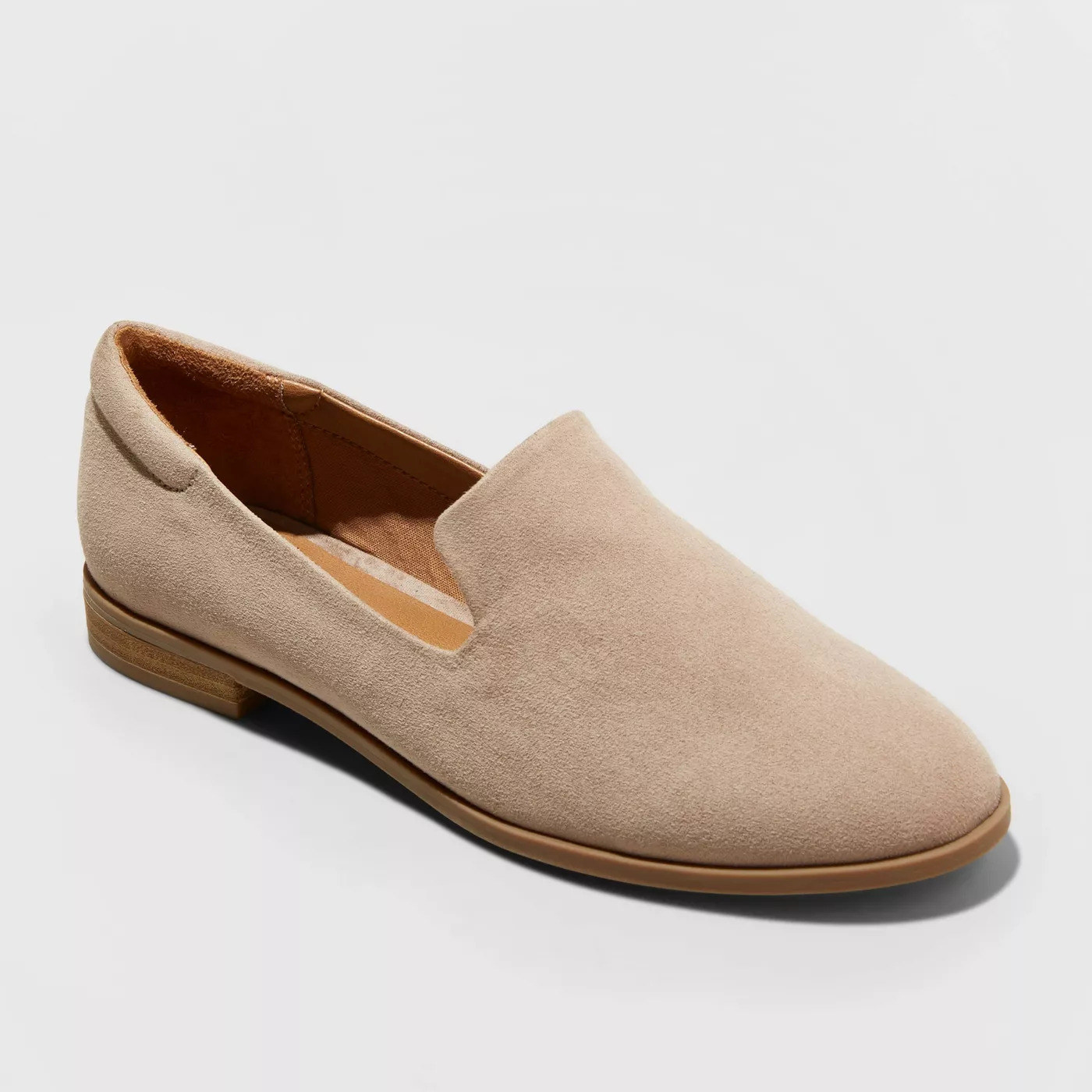 A beige suede loafer with a light brown sole