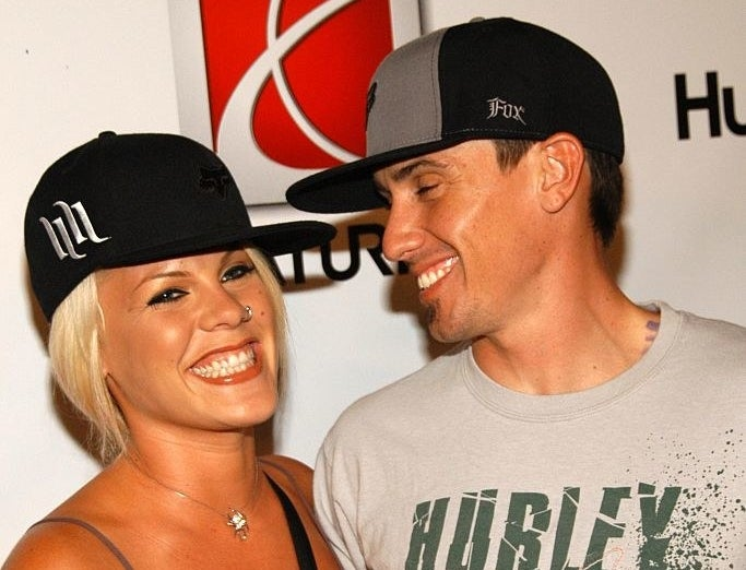 Carey Hart smiling at  Pink while posing together at a Hollywood event