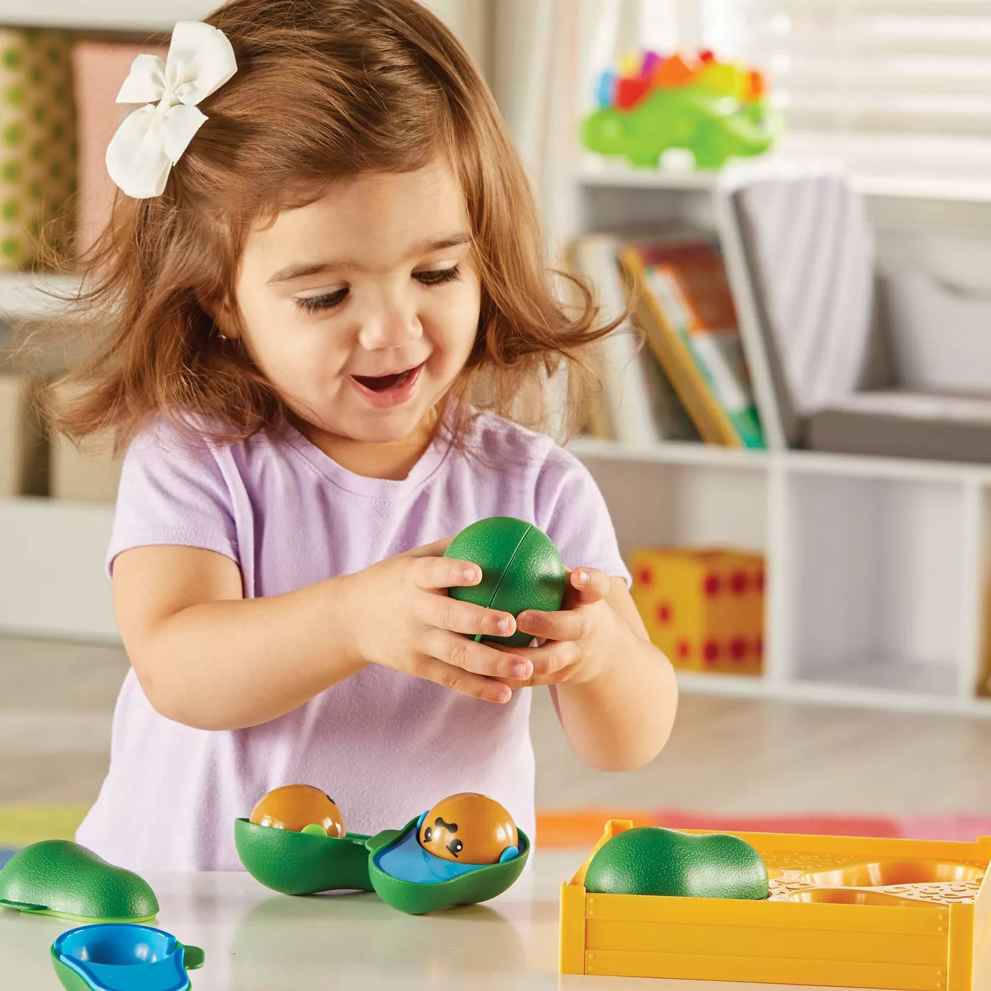 Child model playing with green plastic avocado