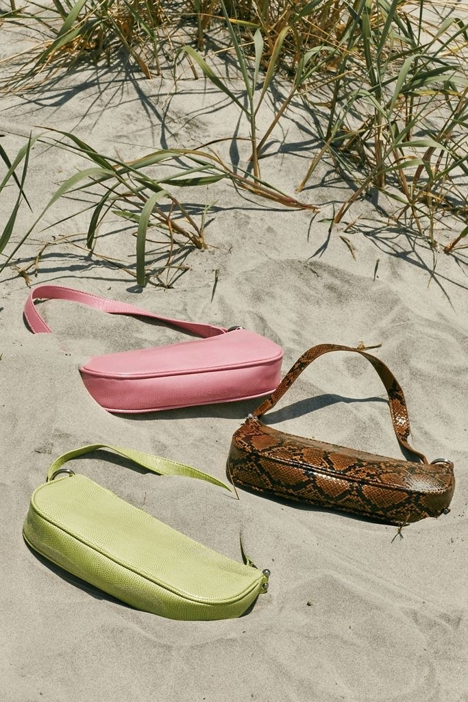 Three of the long, short bags with arm strap in pink, lime green, and brown croc