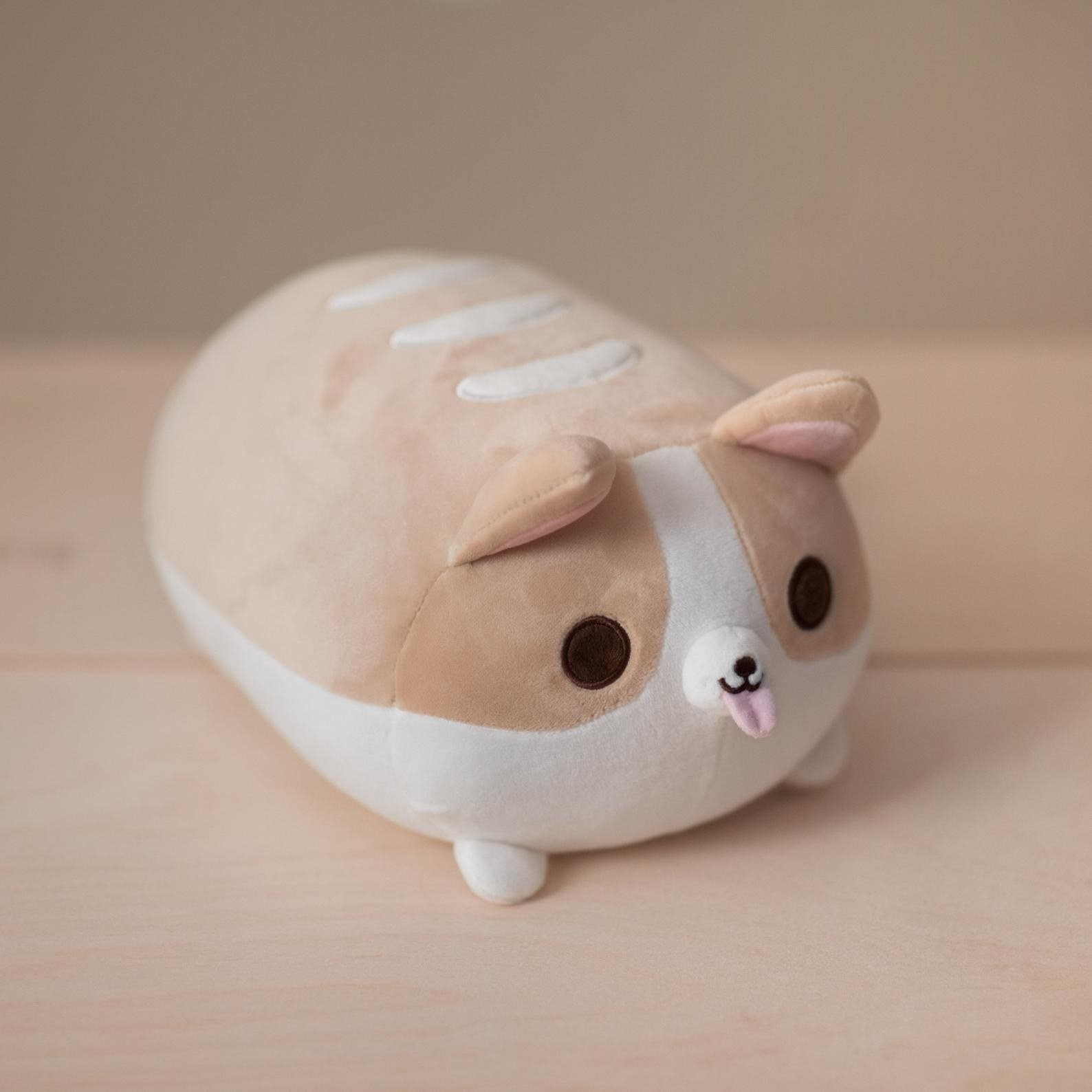 A plush corgi in the shape of a bread loaf