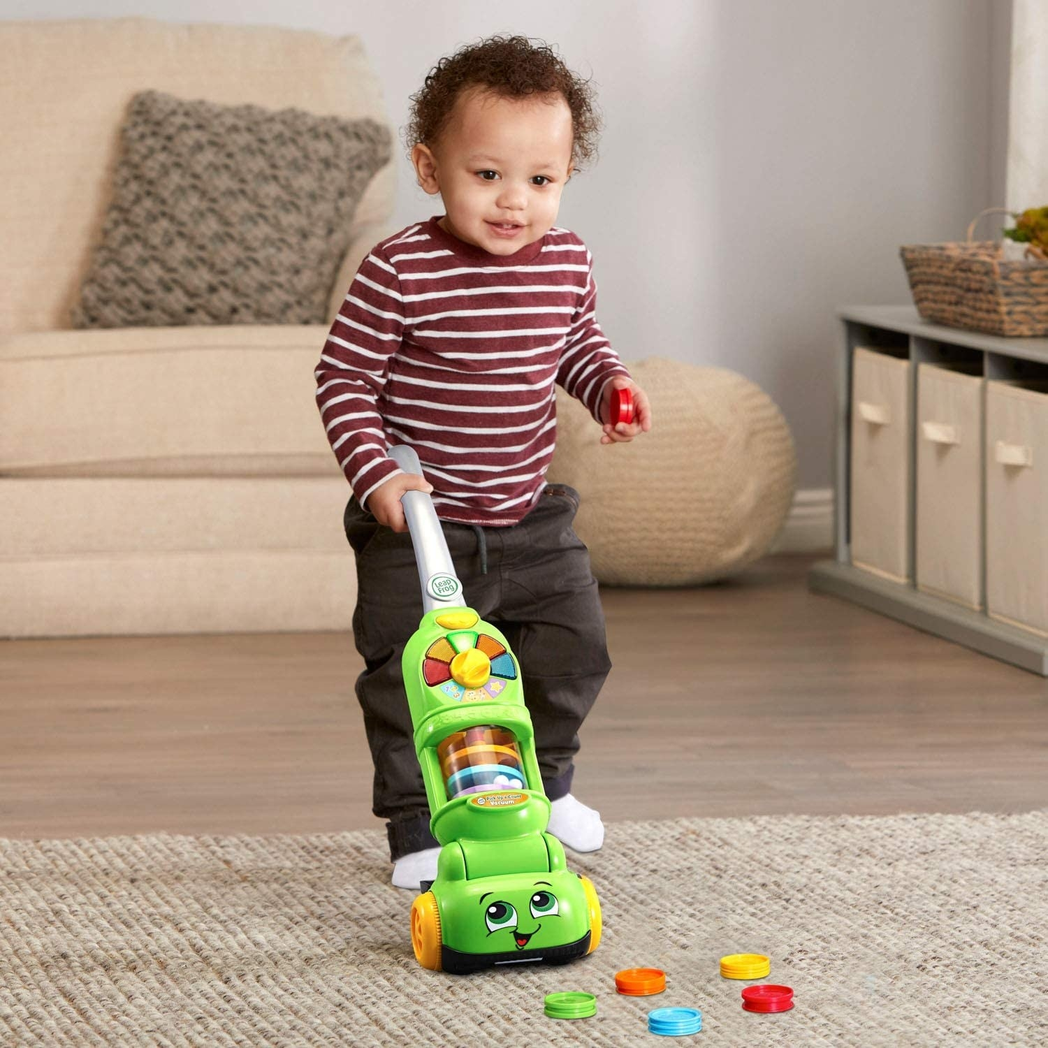 A child model playing with a green plastic vacuum with mult-colored discs