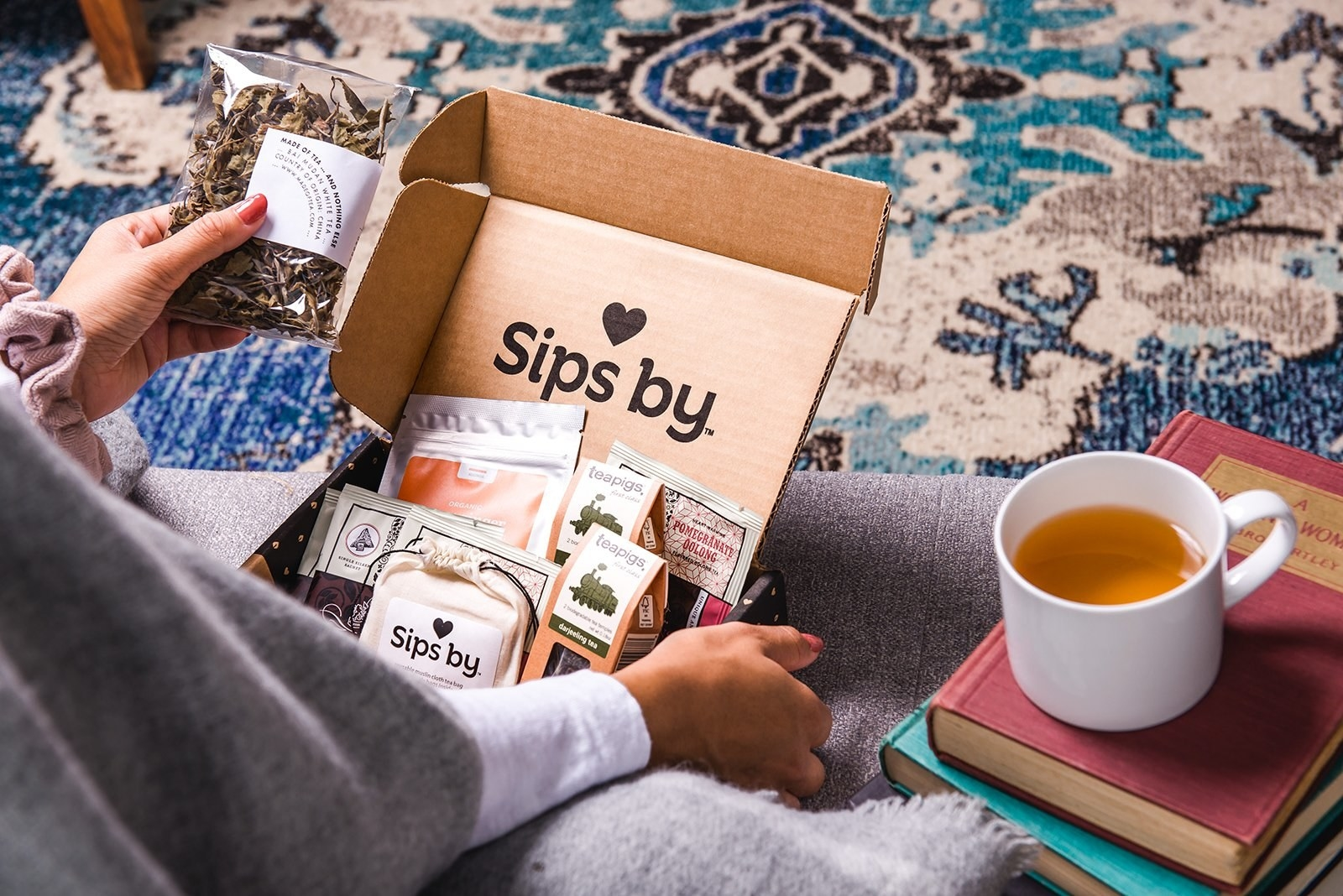 a person reaches for their Sips By box which is filled with teas