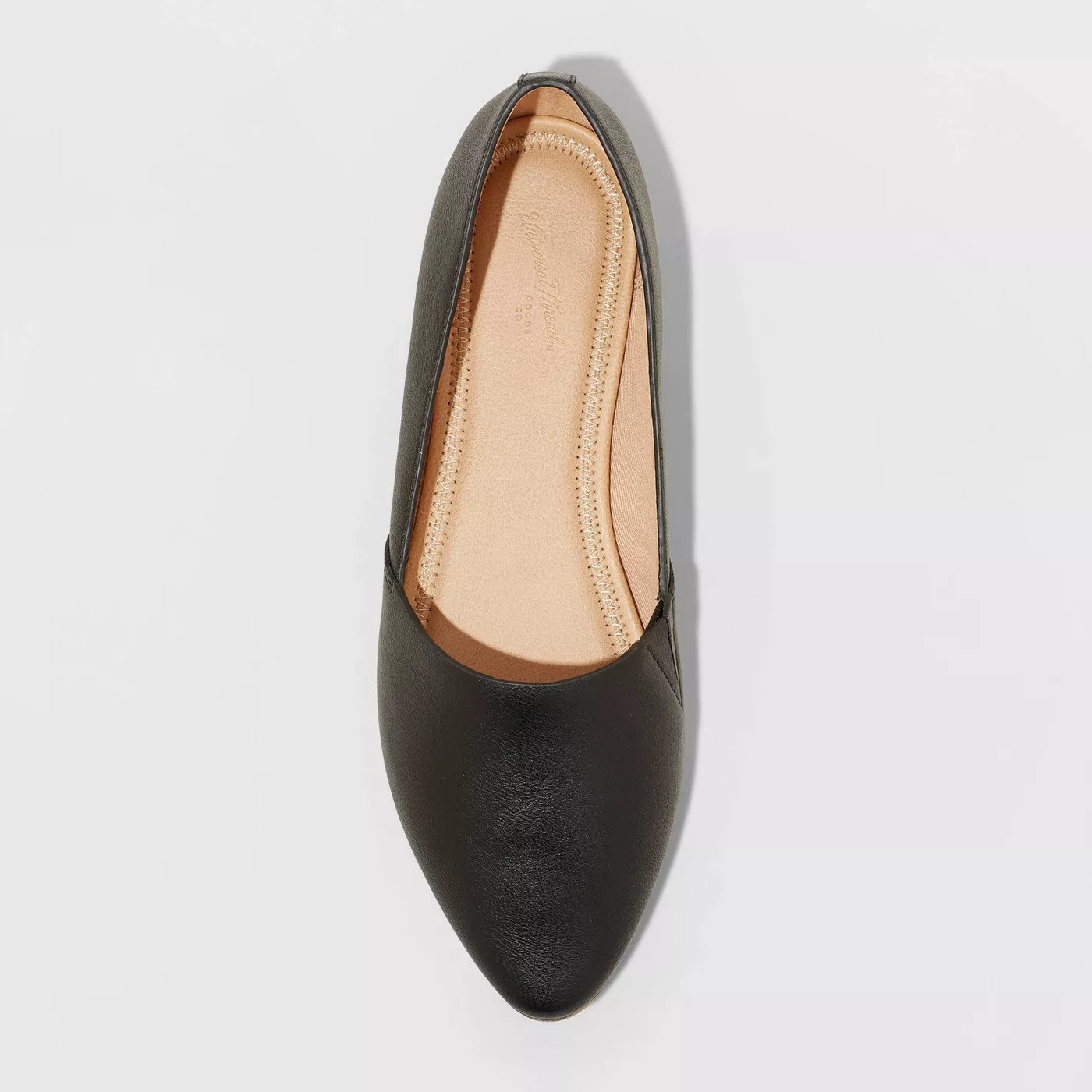 A black faux leather flat with a pointed toe and tan soles