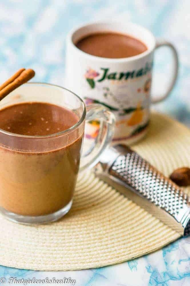 A cup of Jamaican hot chocolate topped with a cinnamon stick.