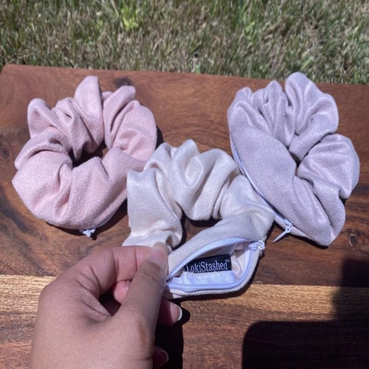 Three scrunchies with zippers in them in pink, purple, and magenta