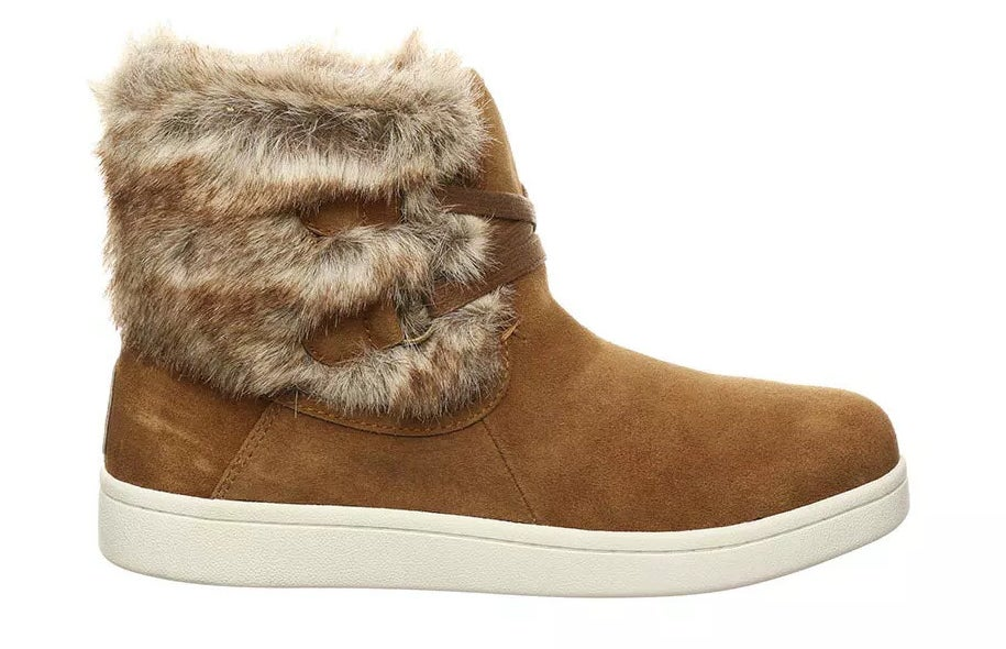 tan suede upper with fur lining, white rubber soles, and tan elastic bands where laces would be.