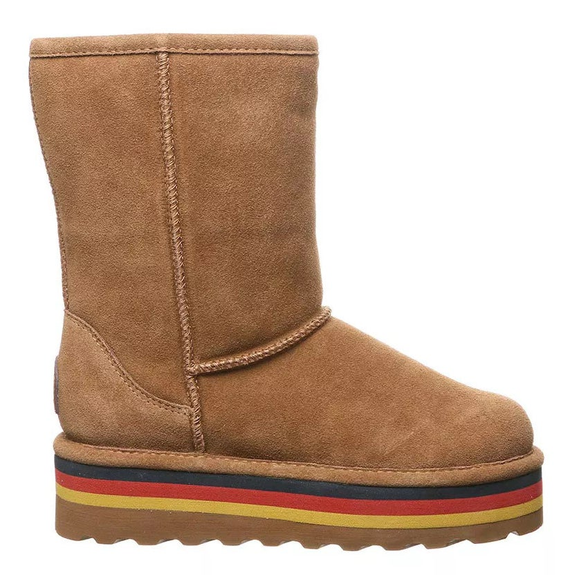 a tan suede sheepskin boot with a tan platform. The platform is adorned with a navy, red, and yellow stripe.