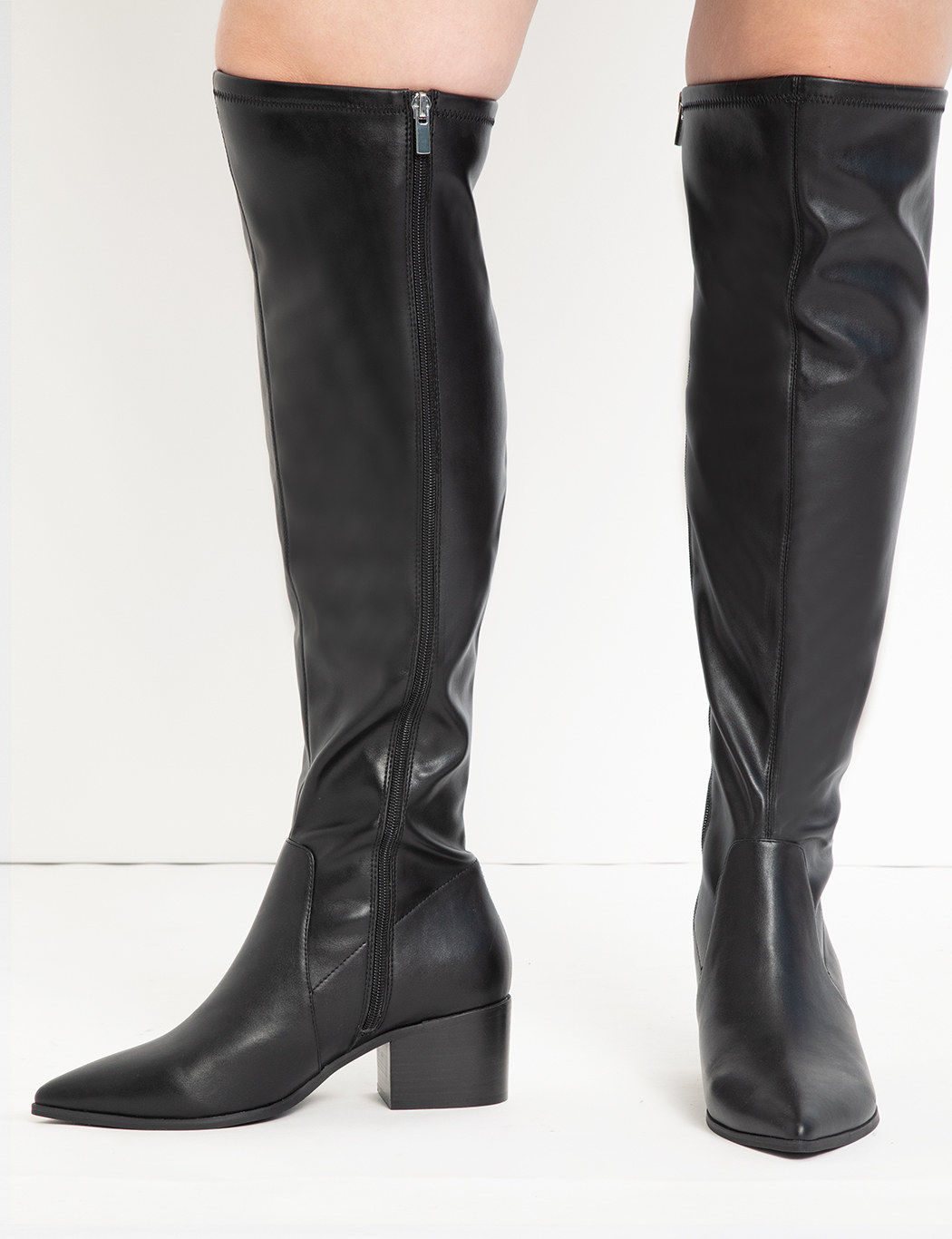 model wearing black pointed toe boots with side zipper