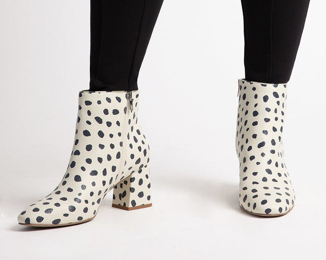 model wearing white ankle booties with black animal print