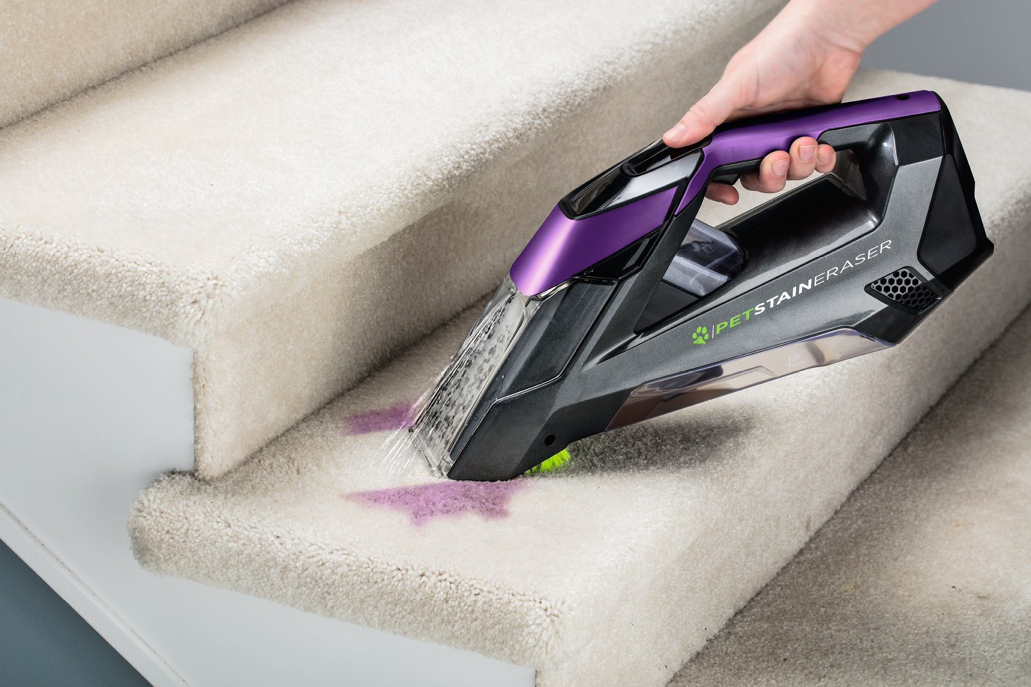 A model using the Pet Stain Eraser cleaner to spray and vacuum a wine stain from off a stair's carpet
