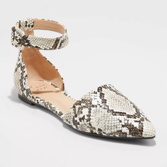 A white and grey snakeskin mary jane shoe with a strap around the ankle