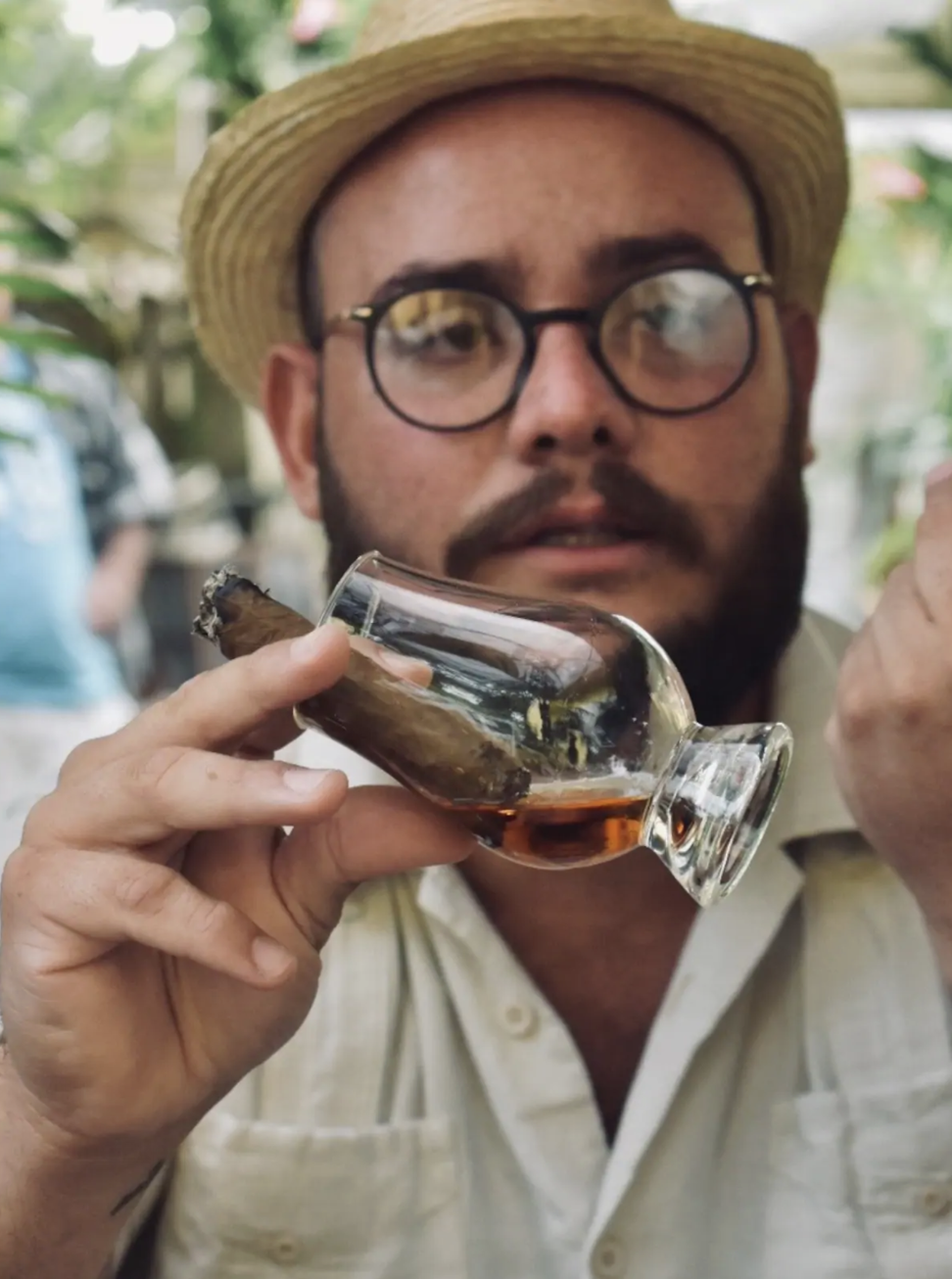 A man in glasses and straw hat looks off camera; a cigar and small cup of rum dangle from his hand in the center of the frame