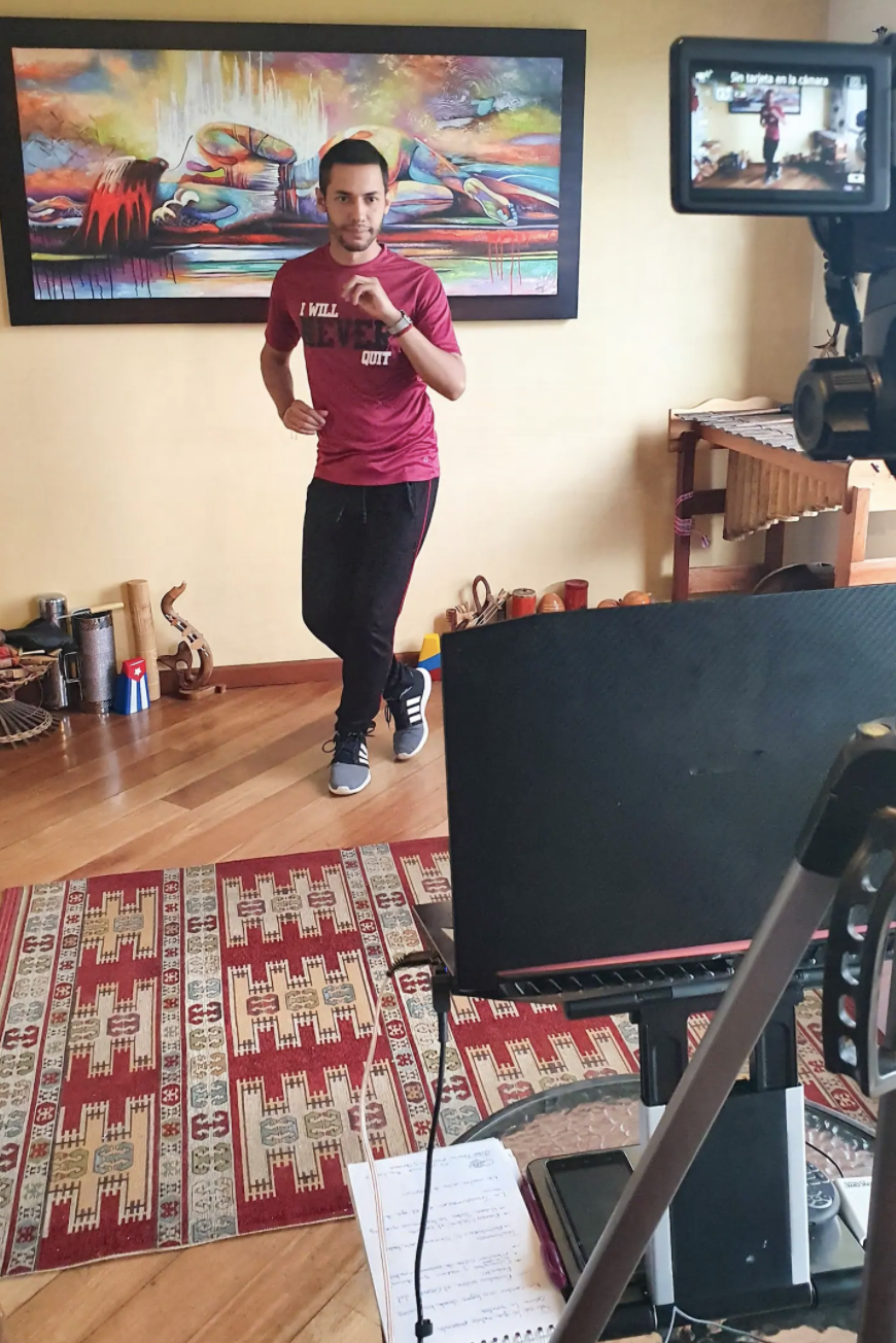 A man in workout clothes dances in front of his laptop camera with a colorful painting behind him