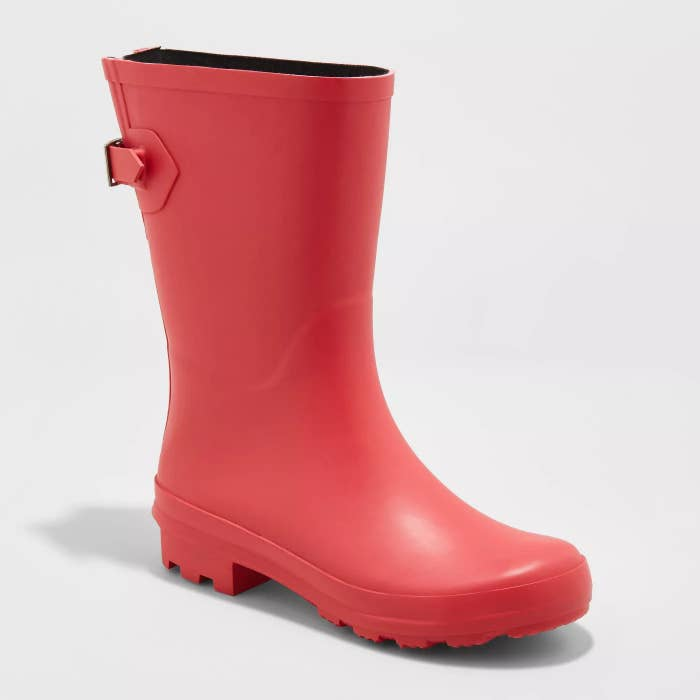 a red rubber rainboot with a buckle and strap in the back