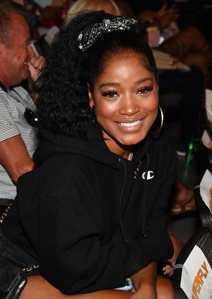 Keke smiling in a sweatshirt with her hair in a ponytail
