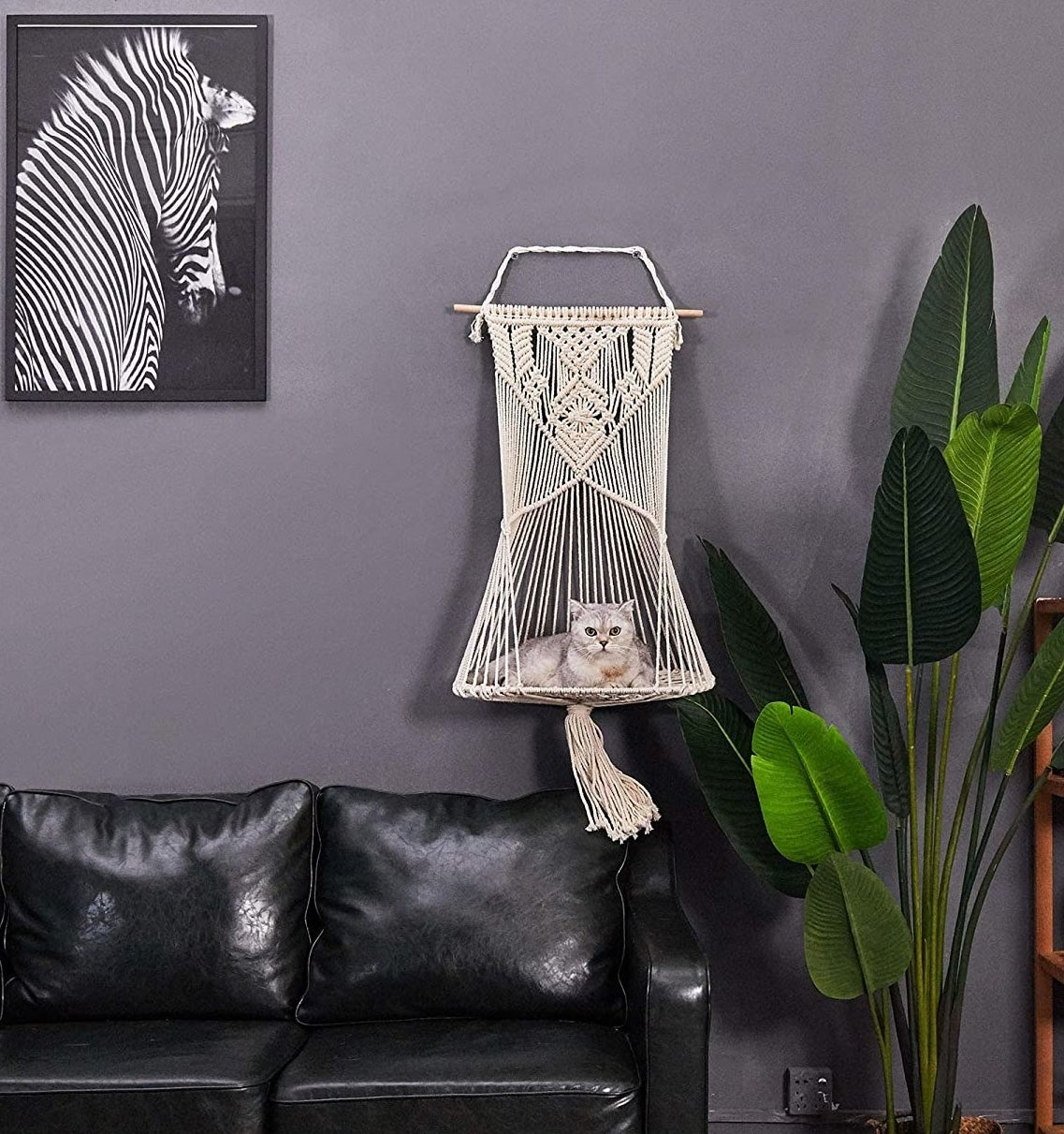 The macrame cat bed, which hangs from a wooden wall mount, ending in a flat woven surface for the cat to lay on