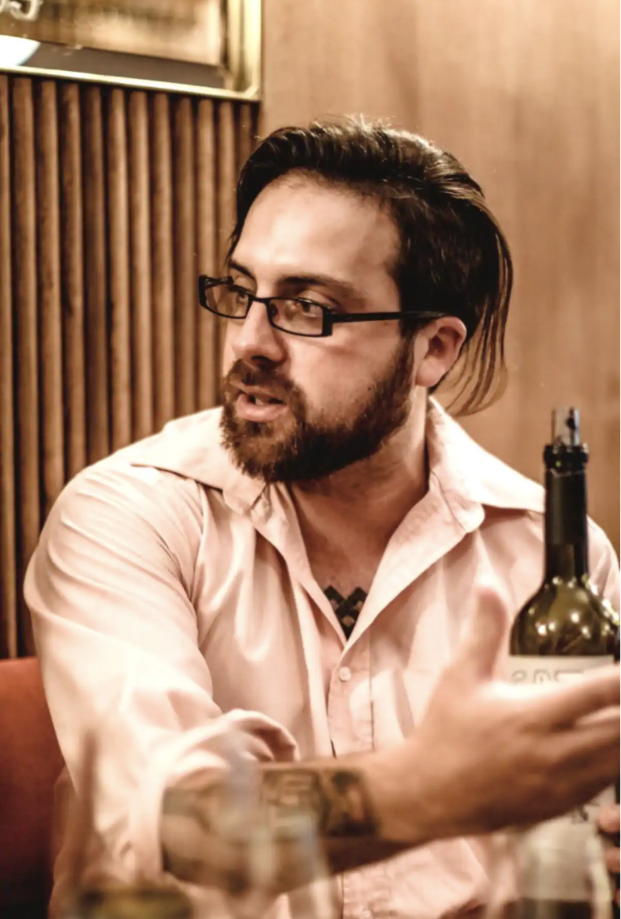 A man in glasses and a button up holds a bottle of wine and gestures as he speaks to someone off camera