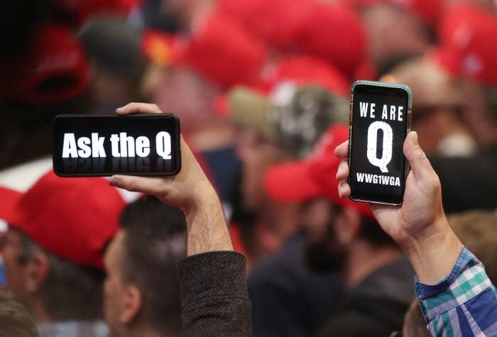 Men hold phones displaying QAnon slogans