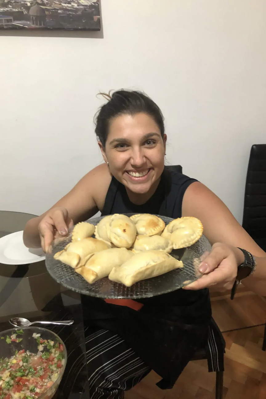 A woman grins to the camera and holds up a clear plate piled with empanadas