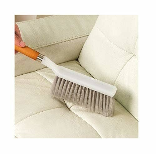 Upholstery brush being used to clean a couch.