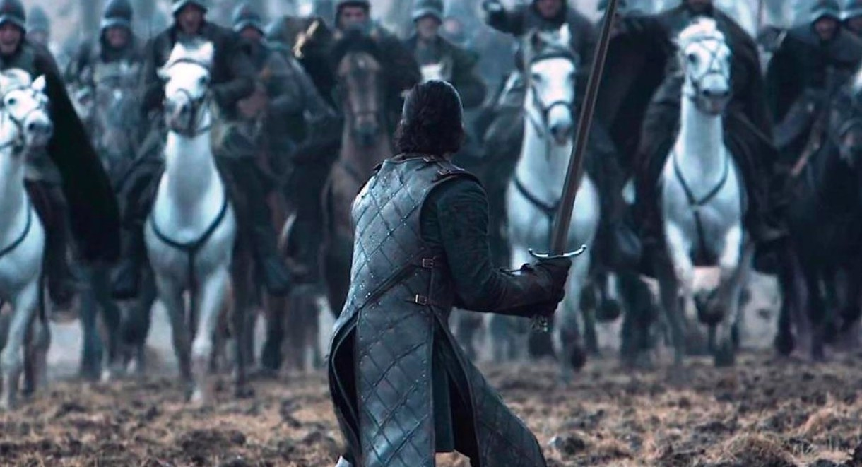 Jon Snow stands alone with his sword, facing an oncoming army on horses
