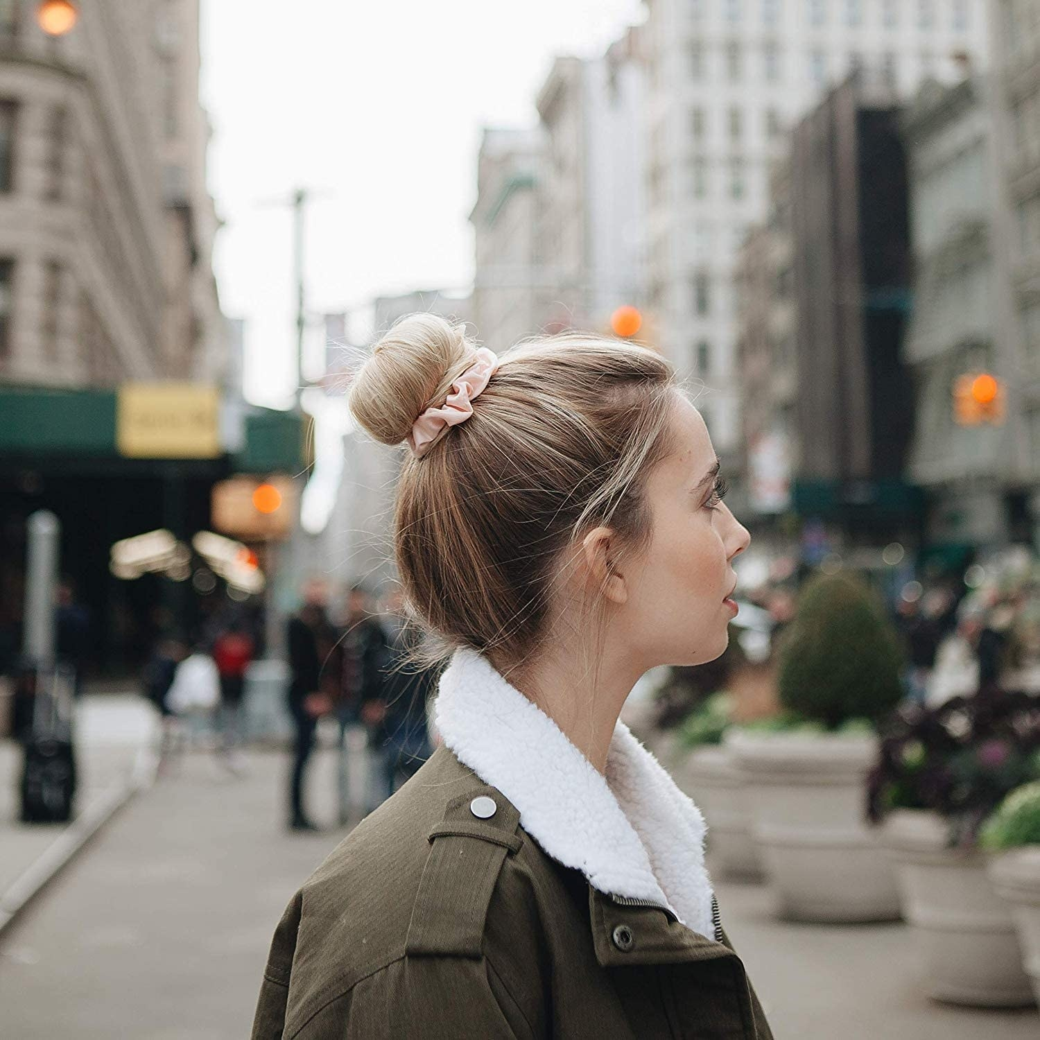 A person using a slim scrunchie to hold their bun in place