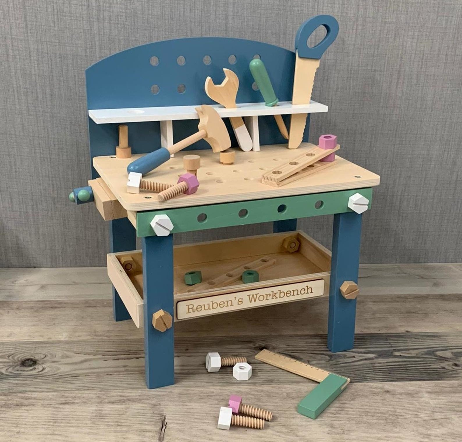 A wooden blue and green toy workbench with various tools
