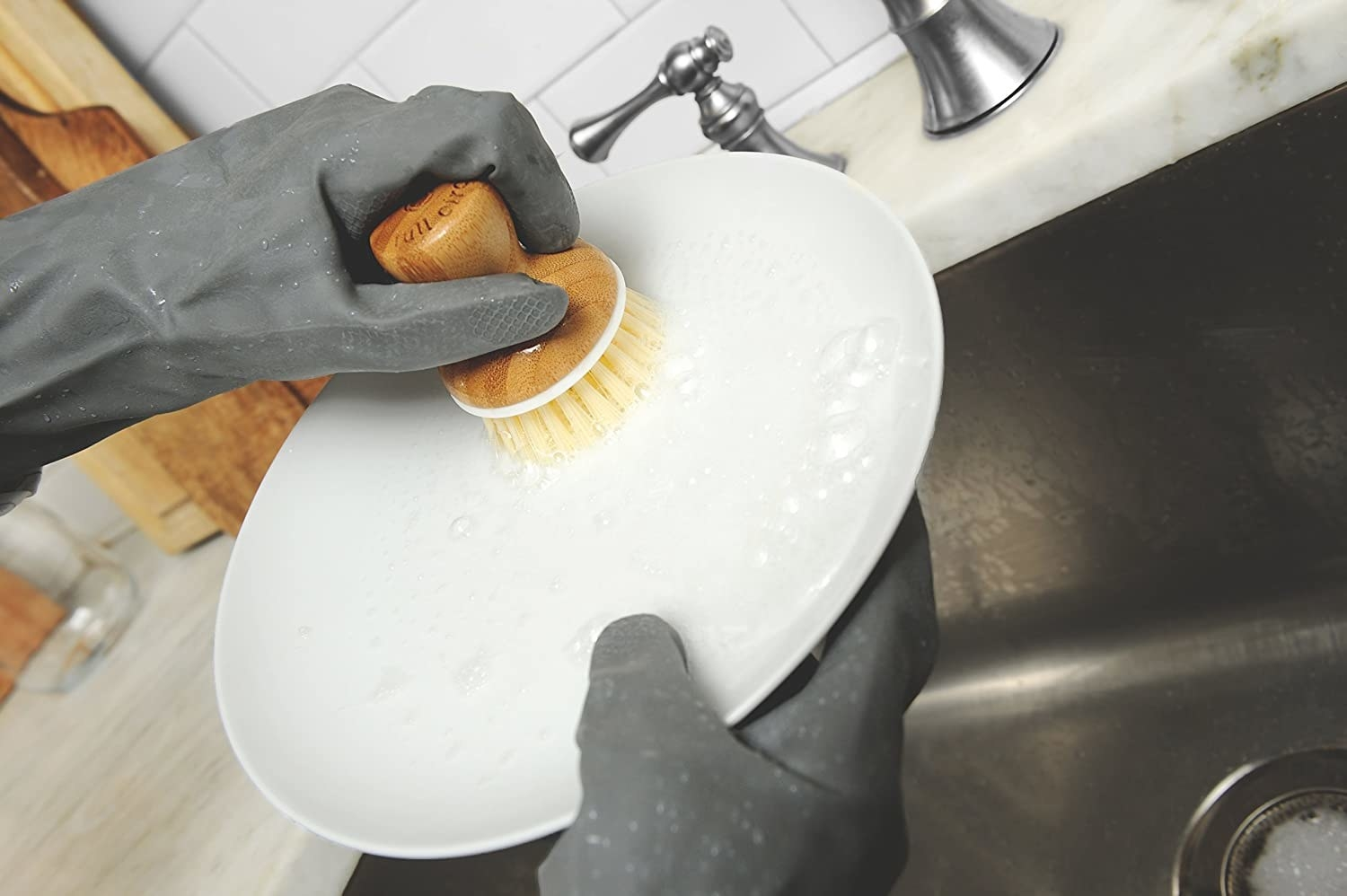 The bamboo-top brush being used to scrub a plate in the sink.