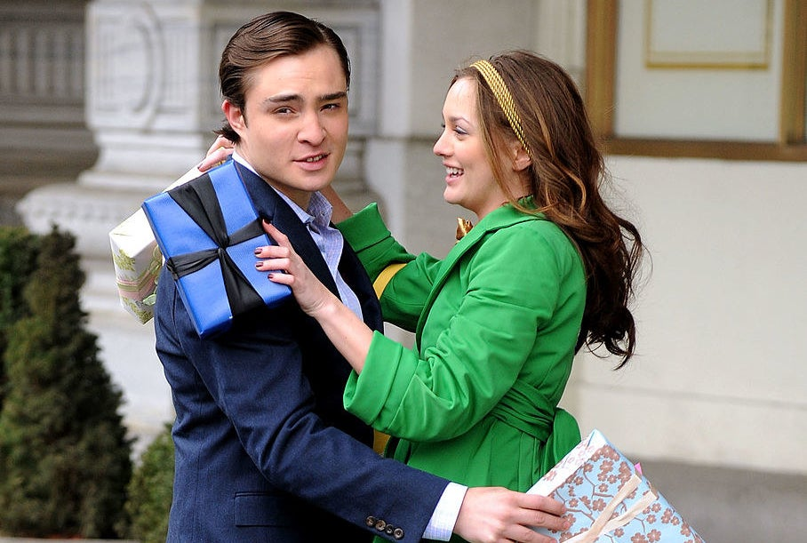 """""""Gossip Girl"""" characters Chuck and Blair embracing in a hug while holding gifts"""