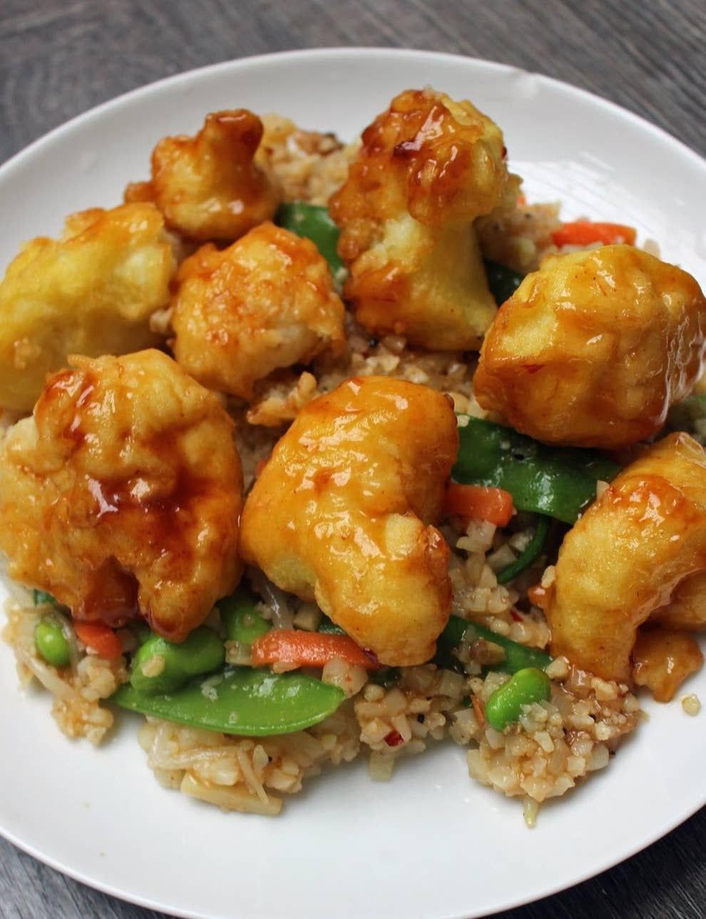 A plate of crispy tempura cauliflower on top of stir fried veggies and cauliflower rice.