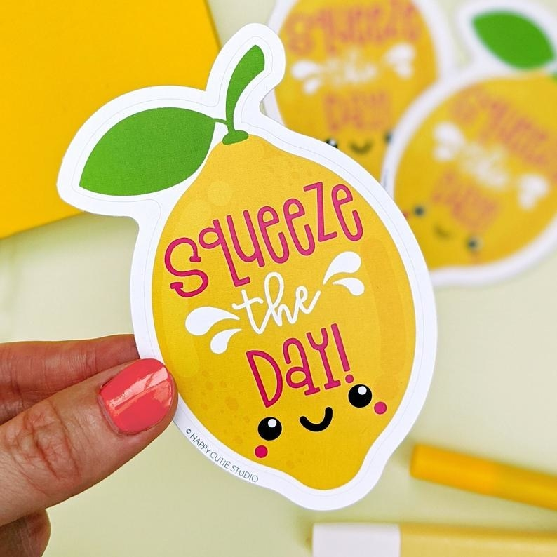 "A large vinyl sticker shaped like a lemon with a happy face that reads ""Squeeze the day!"""
