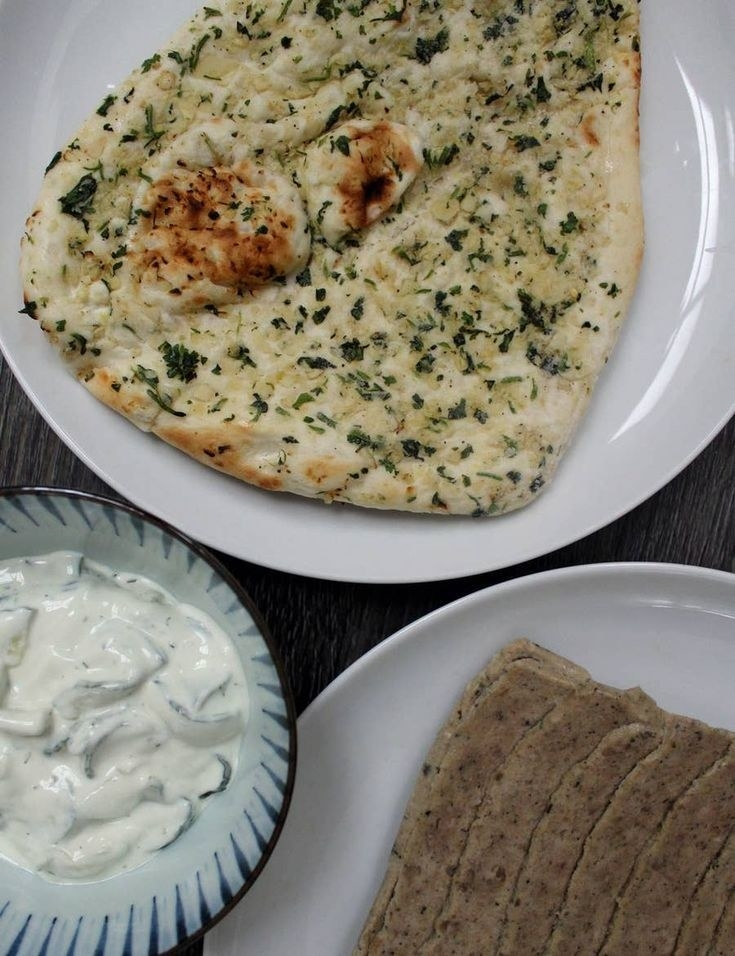 Garlic naan, a bowl of tzatziki, and a plate of sliced gyro.
