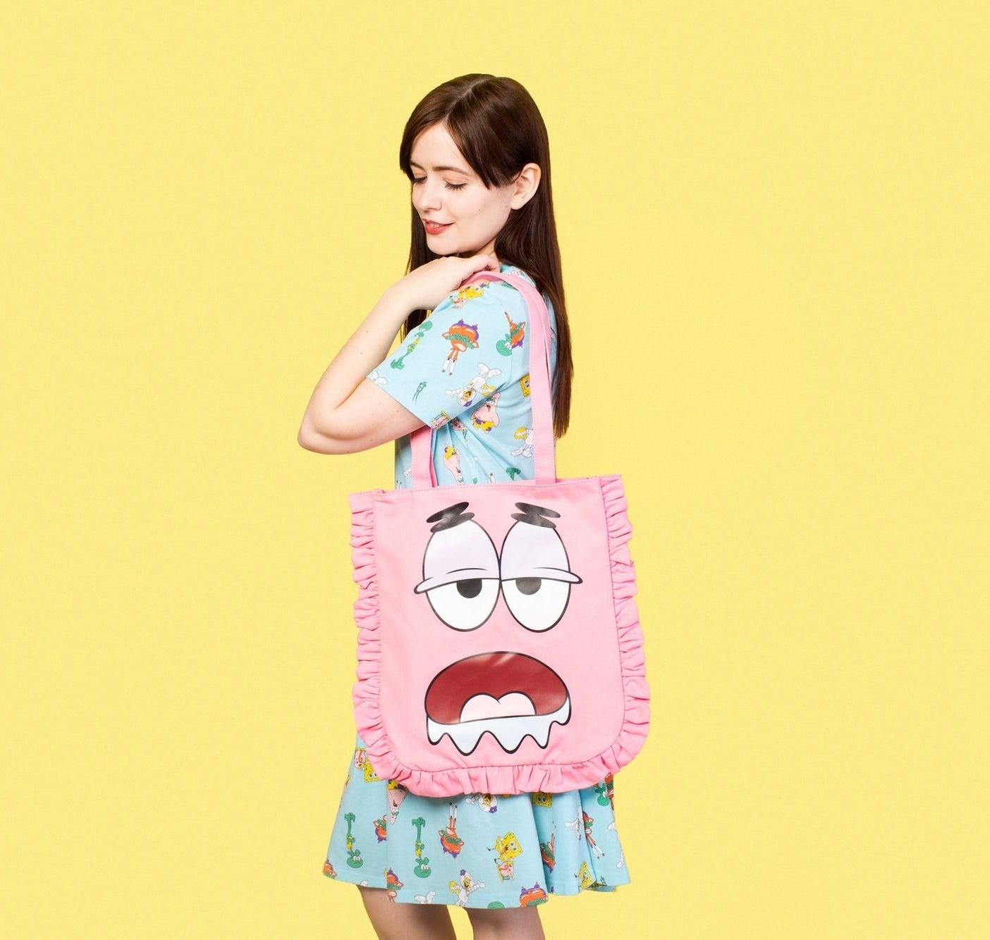 """A model carrying the pink tote with ruffles around the sides and the drooling face of Patrick Star from """"SpongeBob"""" emblazoned on it"""