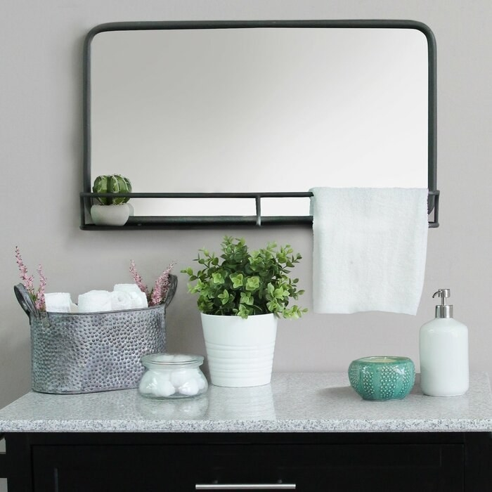The Straley Metal Beveled with Shelves Bathroom/Vanity Mirror installed in a bathroom above a counter