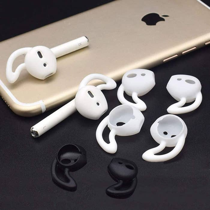 Four sets of silicone ear hooks for AirPods. One pair is on the AirPods and the others are beside an iPhone
