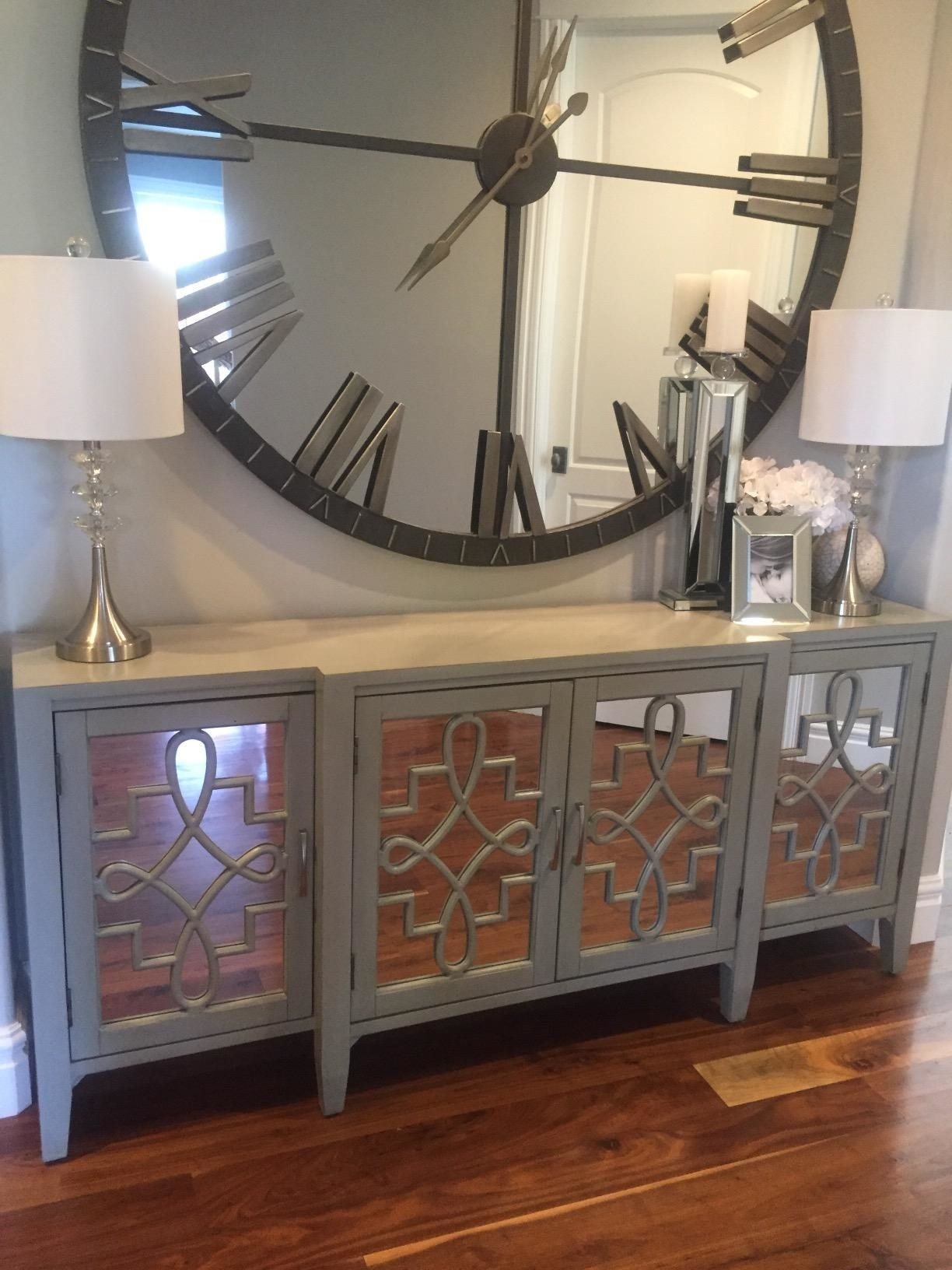 Reviewer pic of the thin wood-top table with four doors in the front with mirrors and a design on top of them.