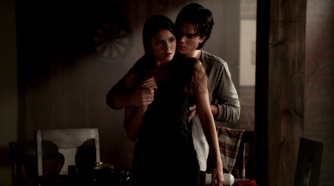 """""""The Vampire Diaries"""" characters Damon and Elena stand in front of each other, as he touches her back and hand"""