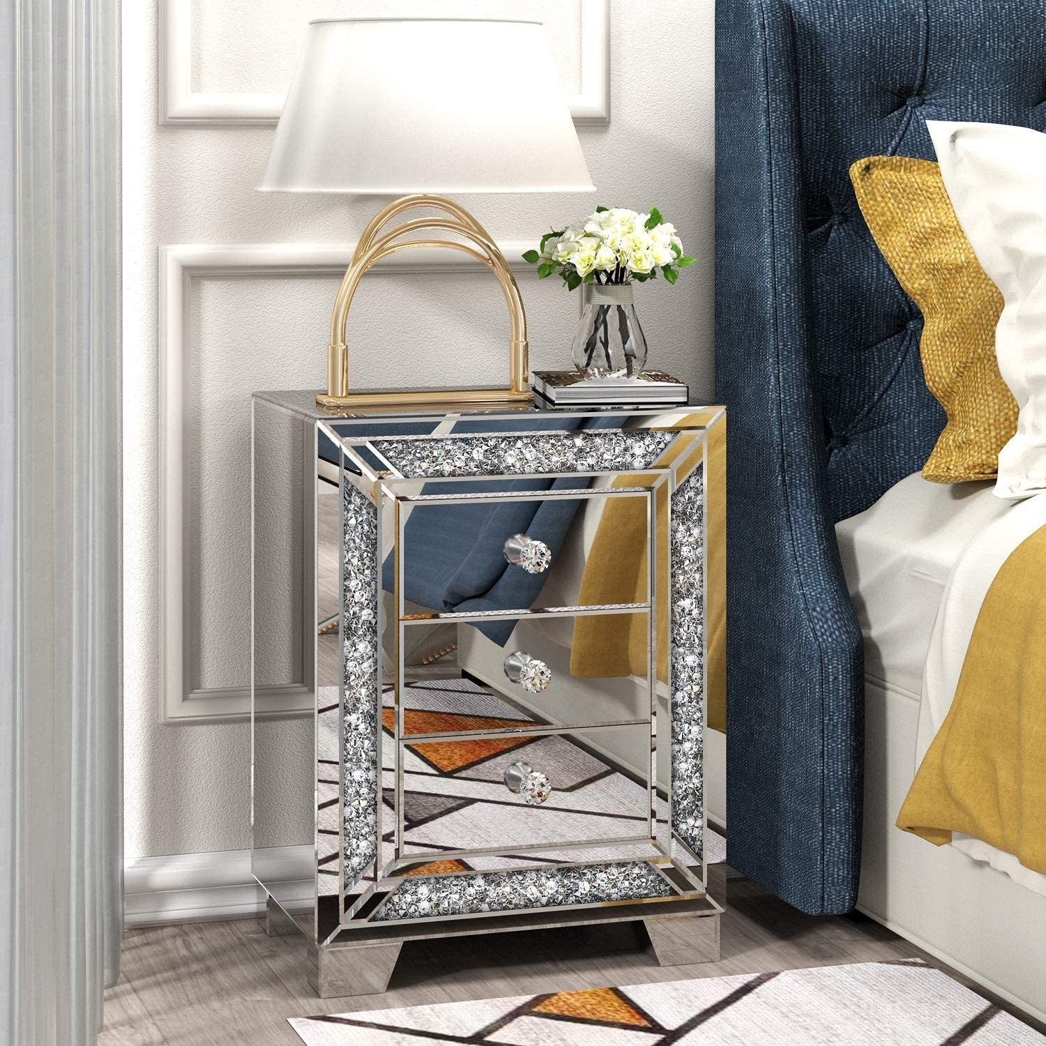 Silver mirrored bedside table with three drawers, a crystal border around the front, and crystal knobs.