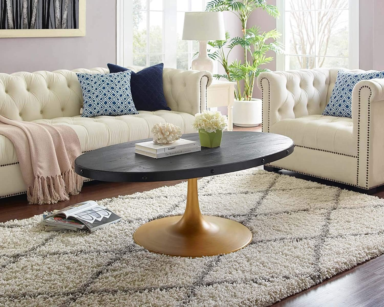 Oval black wood-top coffee table with gold iron pedestal base in a living room.