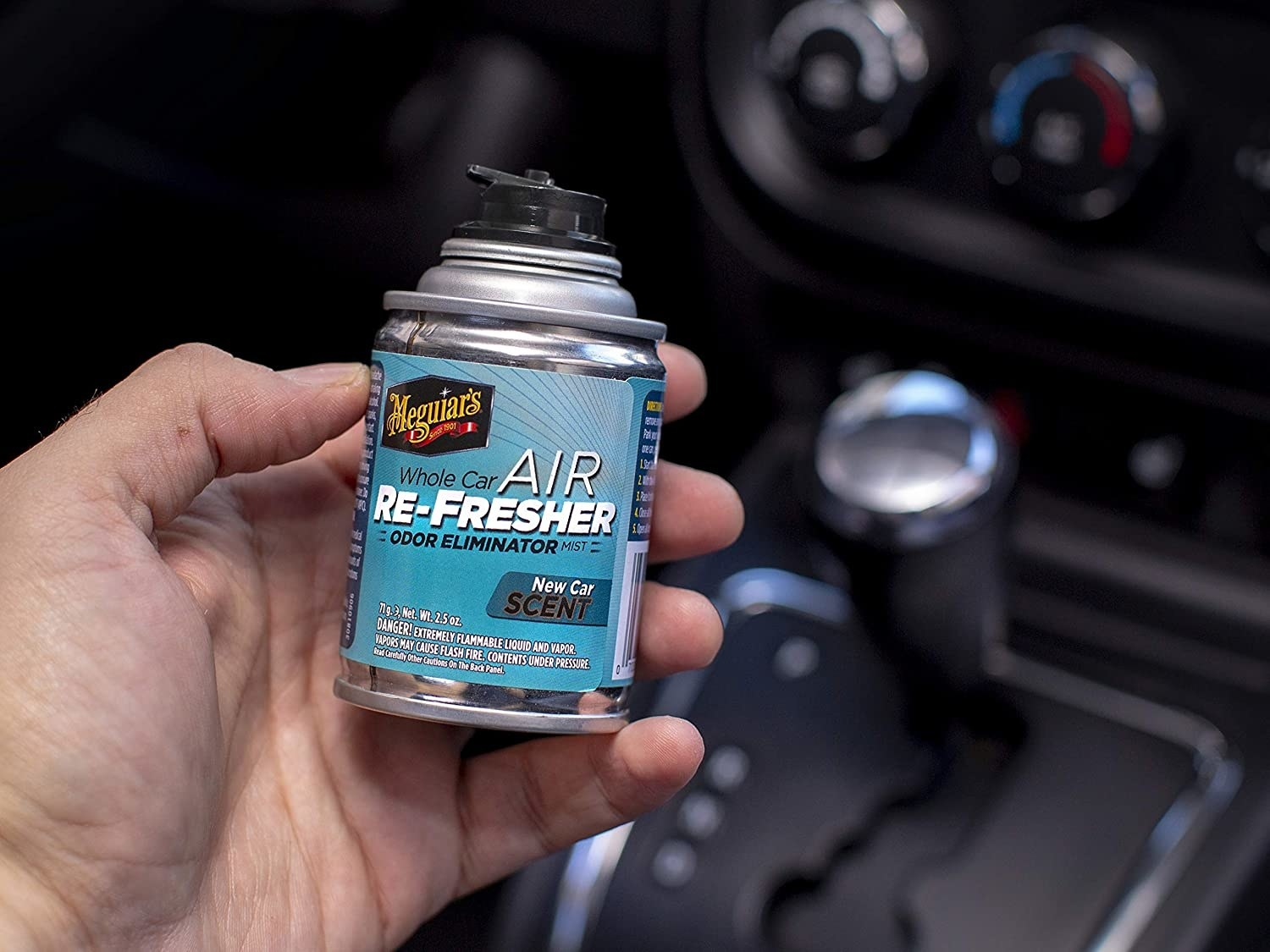 A person holds a small can of the product in a car